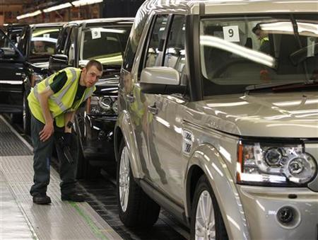 A worker inspects a Land Rover Discovery on the production line at their factory in Solihull