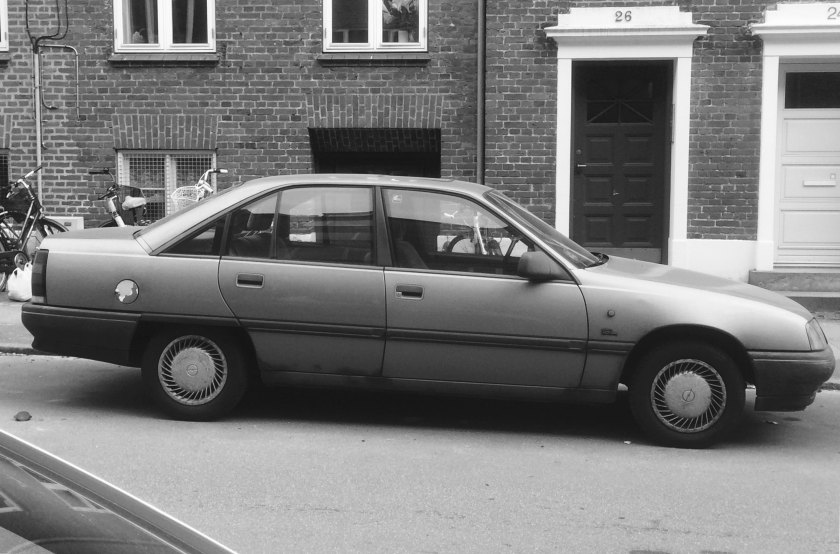 1988 Opel Omega: the base model with no rear armrest or headrestraints. Probably the 2.0 litre four cylinder. These are best understood as shapes inspired by industrial product design and not car design.