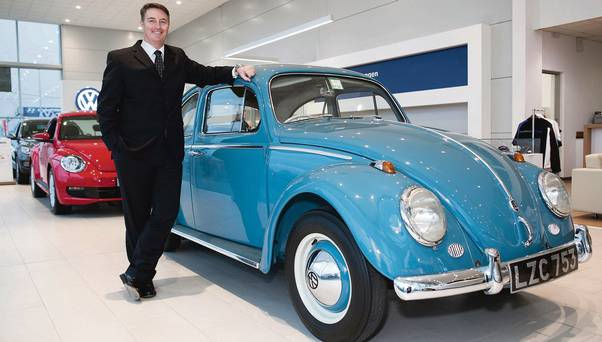 CEO for the VW Group Ireland, Simon Elliot poses with an early Dublin-assembled Beetle. Image via independent.ie